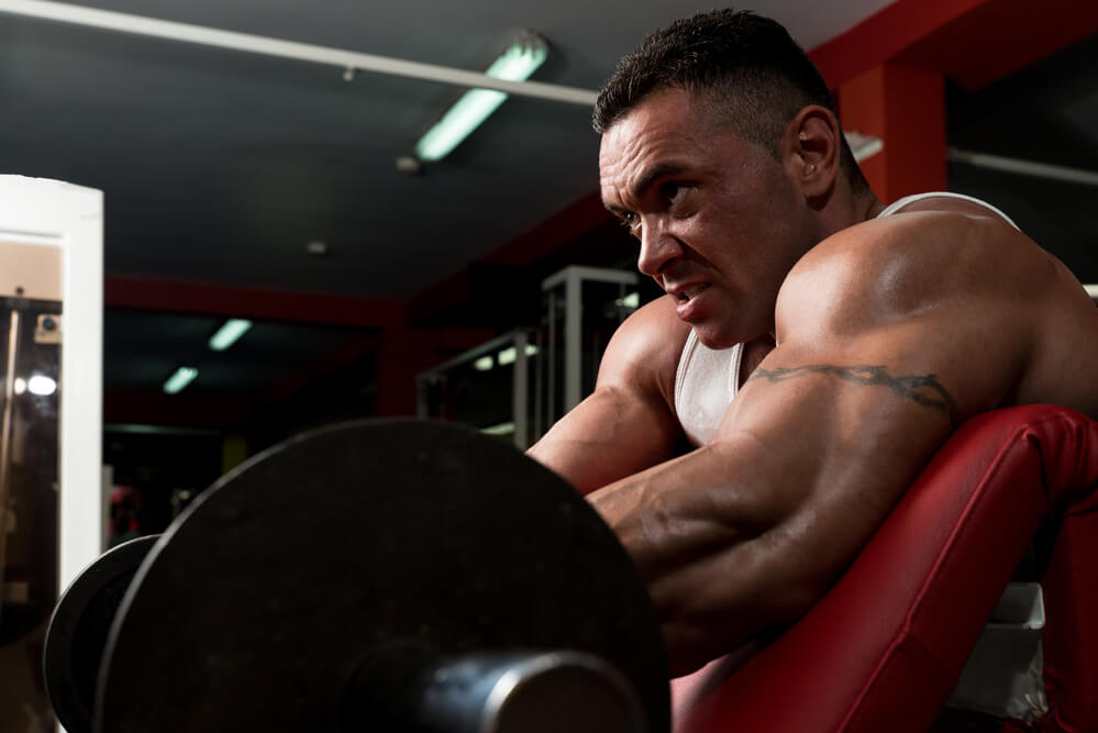 Bodybuilder doing preacher curls